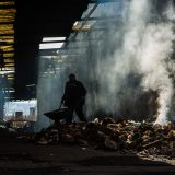 Refugees burning toxic rubbish to keep warm in a derelict railway warehouse at Belgrade Central Train Station