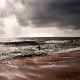 Lone Fisherman under stormy skies